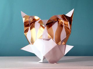 A Golden Snow Owl in Origami, folded with gift-wrapping paper