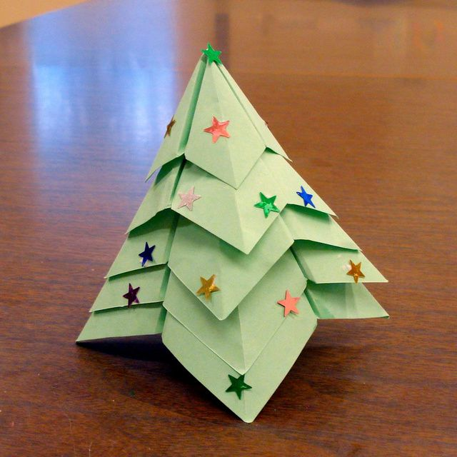 An origami Christmas tree decorated with star stickers.